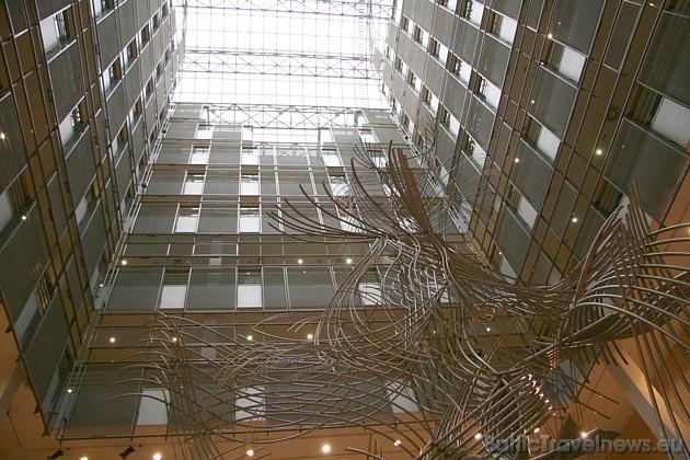Ēkas iekšienē vienmuļo logu virknes pārtrauc metālmākslinieku skulptūra