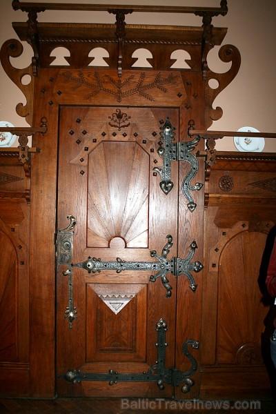 Masīvās durvis ar krāšņajiem metāla apkaluma ornamentiem, liecina par kādreizējo varenību