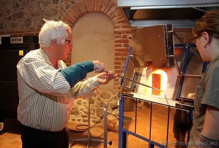 Vecais stikla meistars, trīsreiz pamērcējot stikla kunkuli kausēšanas krāsnī, ķeras klāt pie darba 47105